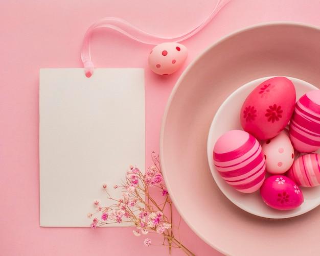 Vista dall'alto di uova di pasqua colorate sul piatto con fiori e carta