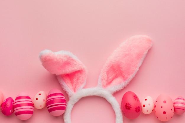 Vista dall'alto di uova di pasqua colorate con spazio di copia e orecchie da coniglio