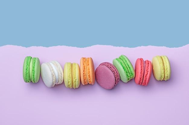Vista dall'alto di biscotti macaron colorati in fila su sfondo a blocchi di colore pastello