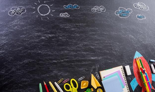 Vista dall'alto di materiale scolastico colorato con libri, matite colorate, calcolatrice, taglierina per penna e clip sullo sfondo del tabellone
