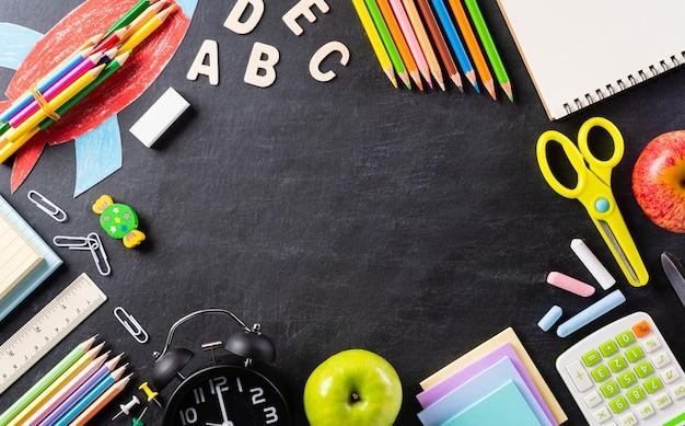 Vista dall'alto di materiale scolastico colorato con libri, matite colorate, calcolatrice, clip, taglierina per penna e mela verde su sfondo tabellone piatto