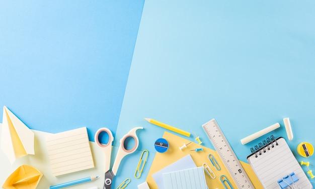Vista dall'alto di materiale scolastico colorato con libri, matite colorate, calcolatrice, taglierina e clip su sfondo di carta pastello
