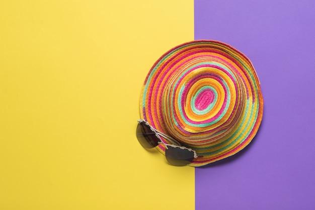 Vista dall'alto di un colorato cappello estivo con gli occhiali su una superficie gialla e viola