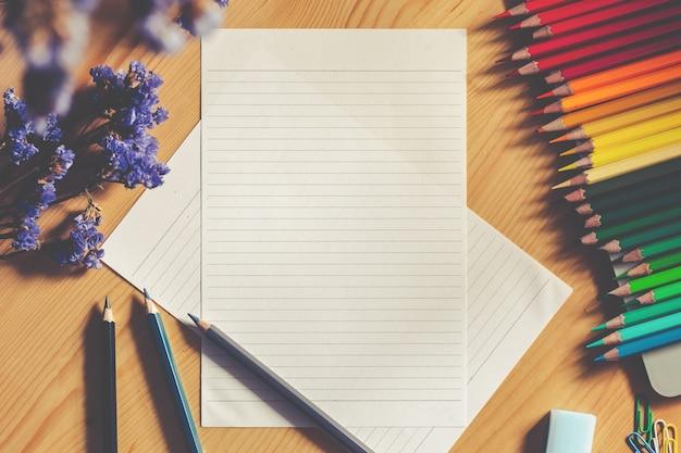 Vista superiore di coloritura delle matite colorate accanto al quaderno di schizzo su fondo di legno