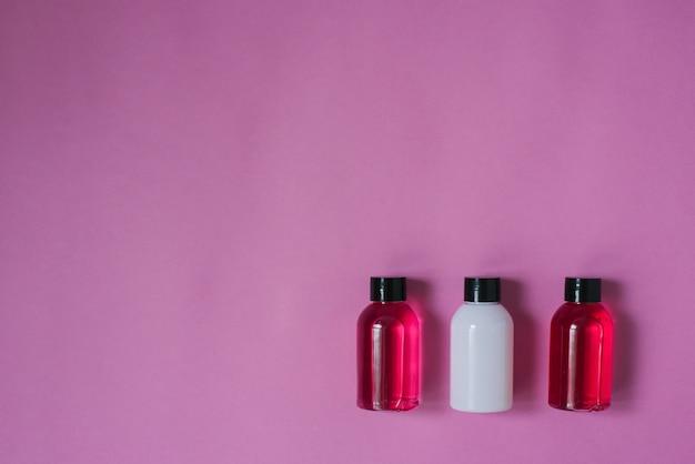 Composizione vista dall'alto di piccole bottiglie da viaggio per cosmetici, gel doccia, shampoo e balsamo per capelli su uno sfondo rosa