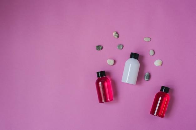 Composizione vista dall'alto di piccole borracce da viaggio per cosmetici, bagnoschiuma, shampoo e balsamo per capelli e ciottoli di mare
