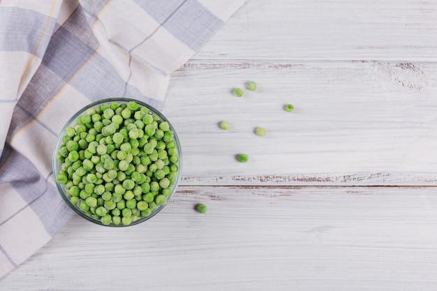 Composizione vista dall'alto con verdure congelate biologiche su uno sfondo di legno bianco