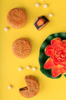 Concetto di vista dall'alto mooncake, torta lunare tradizionale, dessert per il festival di metà autunno su sfondo giallo, primo piano, stile di vita.