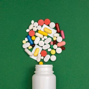 Vista superiore del contenitore che rovescia varietà di pillole
