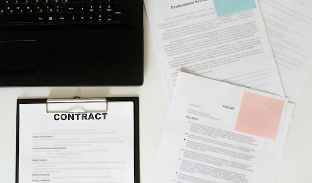 Vista dall'alto del contratto negli appunti che giace in ufficio sul tavolo con laptop e documenti