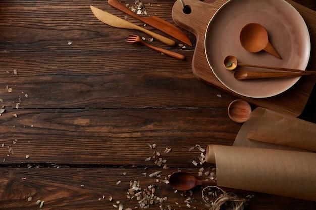 Vista dall'alto di utensili da cucina in legno con spazio per il testo su sfondo di legno