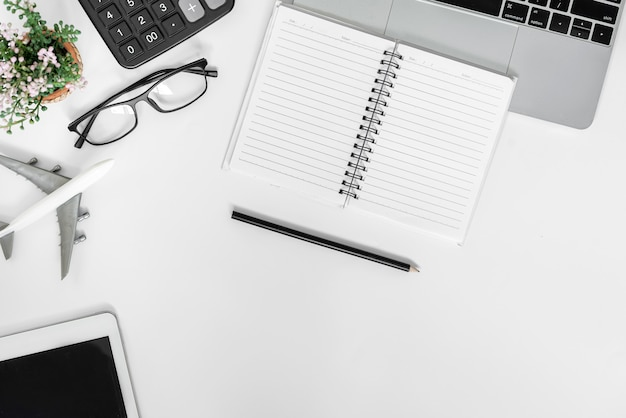 Spazio della copia vista dall'alto. scrivania da ufficio con laptop, blocco note in bianco sulla tavola di legno.