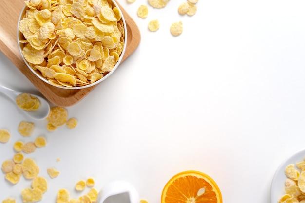 Vista dall'alto di fiocchi di mais ciotola dolci con latte e arancia su sfondo bianco, layout overhead piatto, concetto di design colazione fresca e sana.