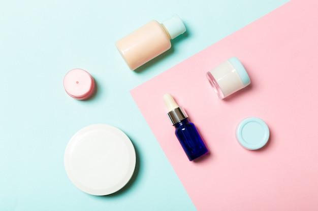 Vista dall'alto di contenitori cosmetici, spray, vasetti e bottiglie su sfondo rosa. vista ravvicinata con spazio vuoto per la progettazione