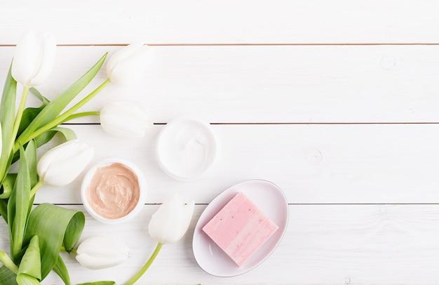 Vista dall'alto di creme cosmetiche e sapone con tulipani bianchi vista dall'alto piatto giaceva su fondo di legno bianco