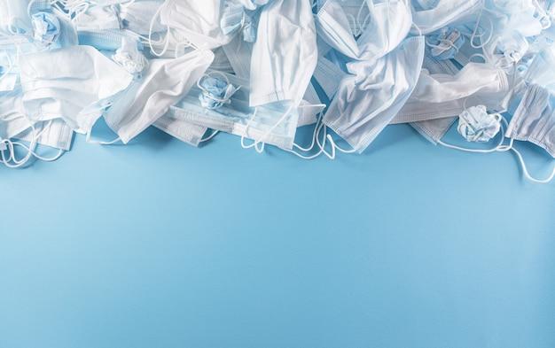 Vista dall'alto delle maschere usa e getta per rifiuti covid19 su sfondo blu pastello