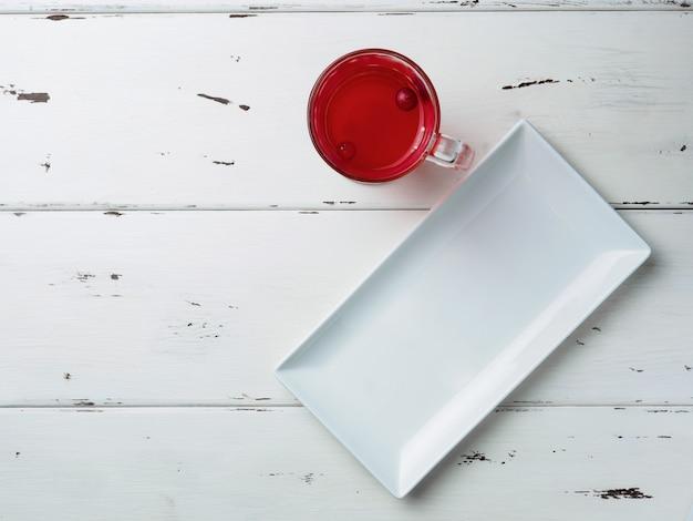 Vista dall'alto sui mirtilli rossi galleggianti in una bevanda rossa fresca in una tazza di vetro