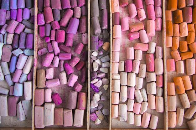 Vista dall'alto di pastelli di pastelli secchi in tonalità calde. i colori rosa, lilla, lilla, arancio si trovano in una scatola di legno. concetto di sfondo del sito web creativo. copyspace