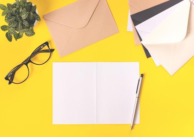 Vista dall'alto dell'area di lavoro creativo con lettera e buste su sfondo giallo. stenditura piatta