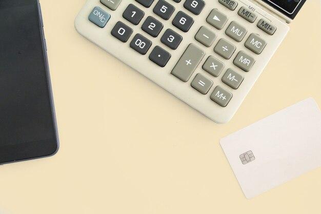 Carta di credito vista dall'alto con calcolatrice e telefono cellulare o telefono. concetto di ufficio di lavoro. concetto di pagamento. conto o finanziario. concetto di acquisto o acquirente. spazio, copia spazio.