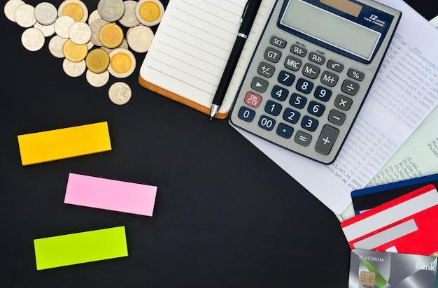 Vista dall'alto di carte di credito libretti calcolatrice taccuino penna pila di monete e foglietti adesivi