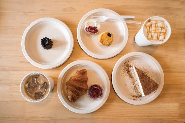 Vista dall'alto di croissant, banana, focaccina, canele sul piatto di carta e caffè freddo sul tavolo di legno nella caffetteria