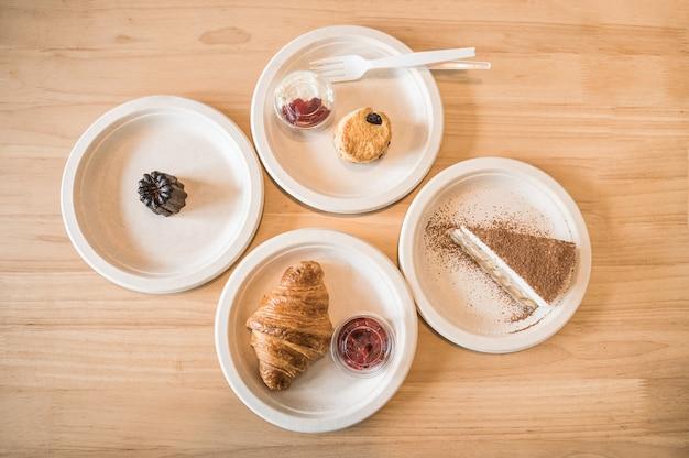 Vista dall'alto di croissant, banoffee, scone, canele sul piatto di carta sul tavolo di legno nella caffetteria