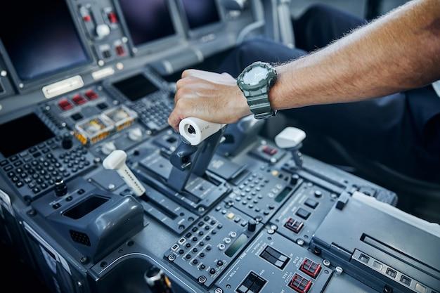 Vista dall'alto testa ritagliata primo piano del livello di commutazione della mano dell'aviatore sul controllo in cabina di pilotaggio durante il volo