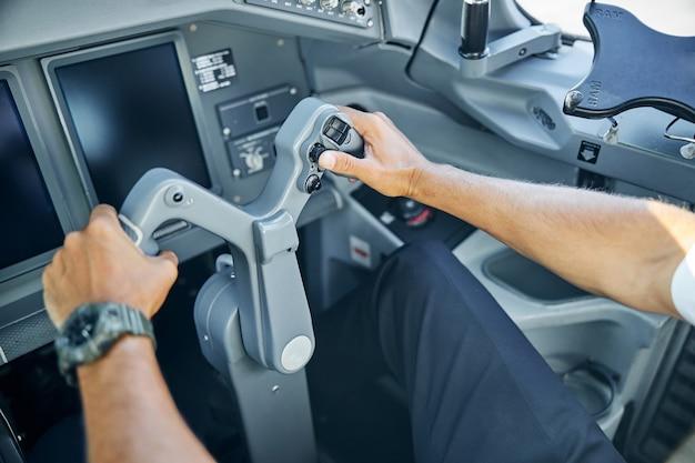 Vista dall'alto testa ritagliata da vicino delle mani dell'aviatore che tengono il timone al controllo durante il decollo
