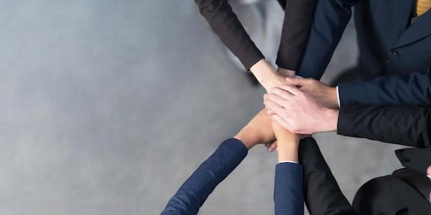 Vista dall'alto, vista ritagliata di un gruppo di persone di affari che mettono le mani insieme, amici con la pila di mani che mostrano unità, lavoro di squadra, successo e concetto di unità