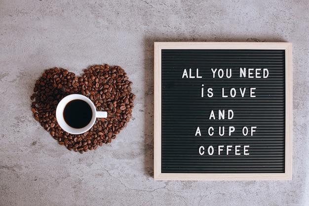 La vista dall'alto di una tazza di caffè a forma di cuore da chicchi di caffè con citazione sulla lavagna dice che tutto ciò di cui hai bisogno è amore e una tazza di caffè