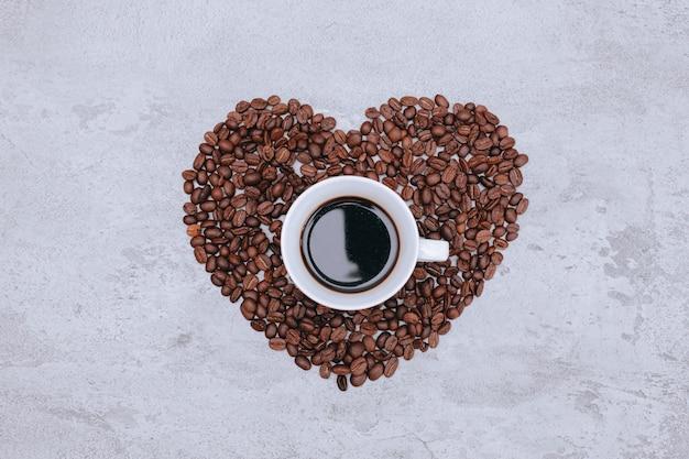 Vista dall'alto di una tazza di caffè sulla bella forma di cuore da chicchi di caffè