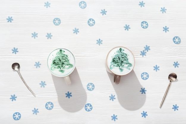 Vista dall'alto della tazza di caffè cappuccino con motivo albero di capodanno su tavolo di legno bianco