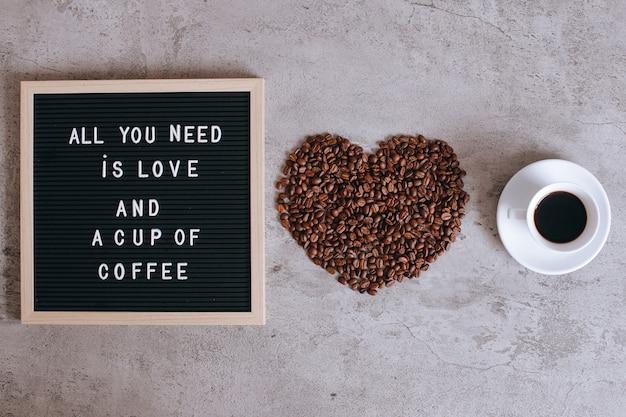 Vista dall'alto di una tazza di caffè e forma di cuore da chicchi di caffè con citazione sulla lavagna, tutto ciò di cui hai bisogno è amore e una tazza di caffè
