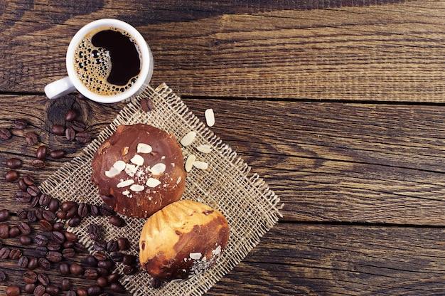 Vista dall'alto su una tazza di caffè e gustosi cupcakes al cioccolato su fondo in legno