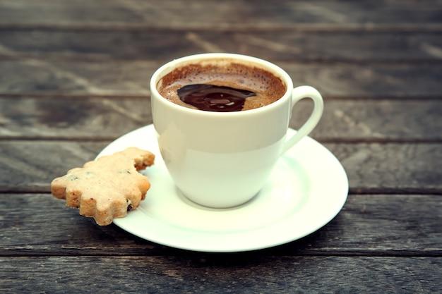 Vista dall'alto di una tazza di caffè su uno sfondo di legno. piccolo caffè espresso nero forte su fondo di legno.
