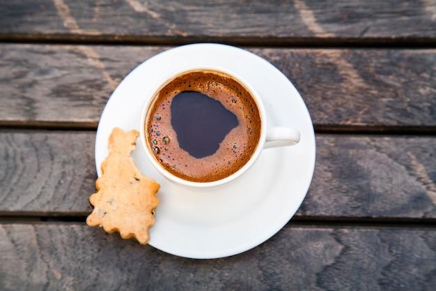 Vista dall'alto di una tazza di caffè su uno sfondo di legno. piccolo caffè espresso nero forte sulla tavola di legno.