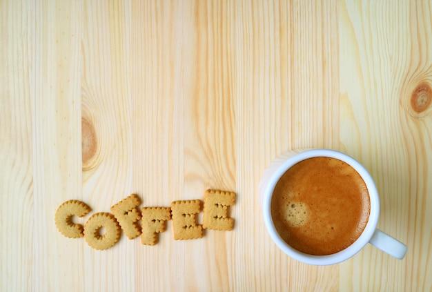 Vista dall'alto di una tazza di caffè caldo sulla tavola di legno con la parola caffè a base di biscotti