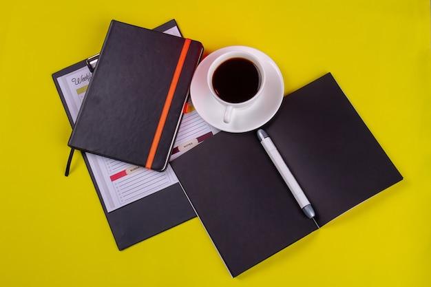 Vista dall'alto tazza di caffè forte con libri e penna.