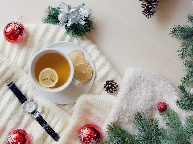 Vista dall'alto tazza di tè decorata - sciarpa lavorata a maglia, rami di abete e pigne.