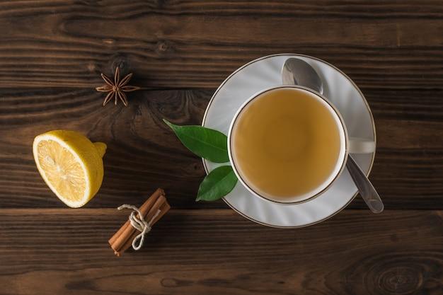 Vista dall'alto di una tazza di tè con limone e cannella su un tavolo di legno. una bevanda tonificante utile per la salute.