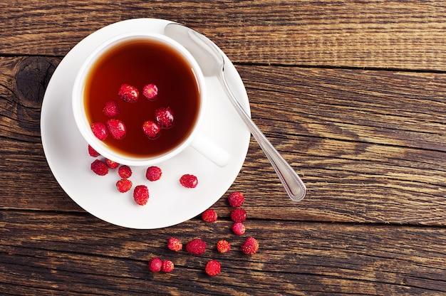 Vista dall'alto di una tazza di tè con fragoline di bosco