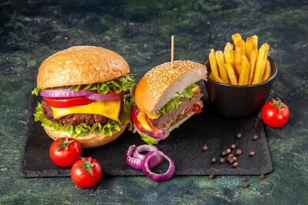 Vista dall'alto di deliziosi panini e pomodori interi tagliati con patatine fritte di cipolle di gambo sul vassoio nero su superficie scura