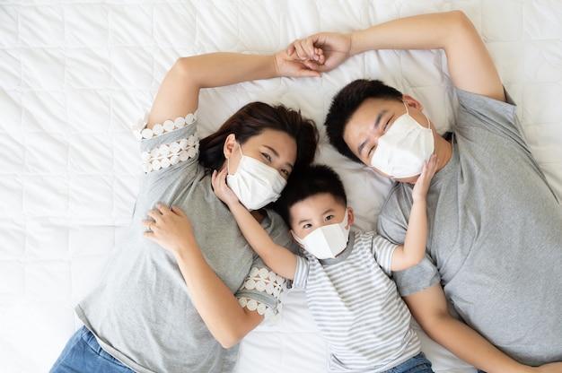 Vista dall'alto del ragazzino sveglio e dei suoi genitori asiatici che guarda l'obbiettivo e indossa la maschera