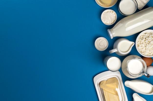 Vista dall'alto di latticini su blu, assortimento di latte, burro, panna acida e yogurt