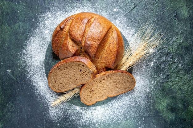 Vista dall'alto pane scuro con farina sulla scrivania scura
