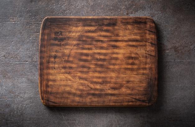 Vista dall'alto di un tagliere rettangolare in legno rustico vuoto marrone scuro con bordi arrotondati su uno sfondo metallico nero