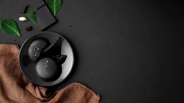 Vista superiore dei macarons del cioccolato fondente sulla banda nera sulla tavola scura