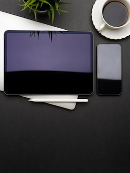 Vista dall'alto dell'area di lavoro piatta e creativa scura con tavoletta digitale, smartphone, laptop, tazza di caffè e spazio di copia