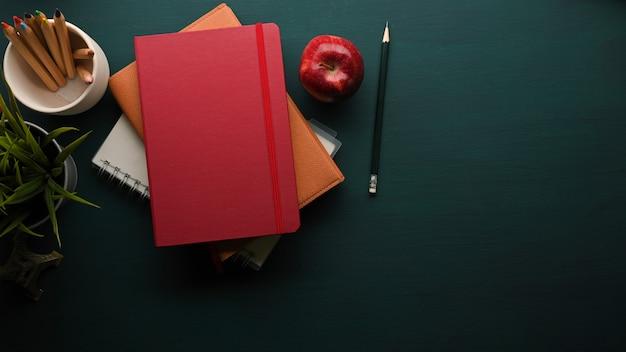 Vista dall'alto del tavolo verde scuro con una pila di libri